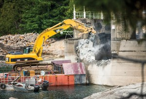 A barge-mounted excavator hammers away at Glines Canyon Dam, the largest dam removal in U.S. history. Elwha River, Olympic National Park, Washington in a scene from DAMNATION. Photo: Ben Knight