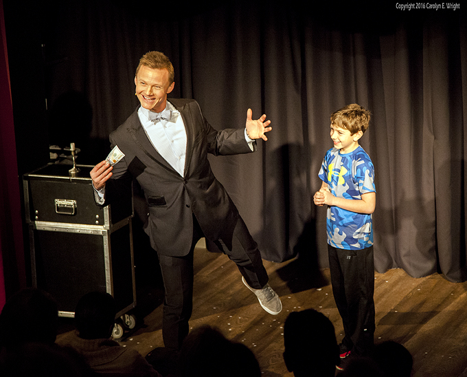 Magician Joel Ward makes Ladonon's $100 bill disappear and then reappear. Photo Copyright 2016 Carolyn E. Wright