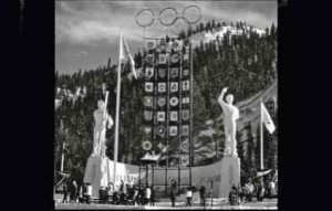 Walt Disney's realization of the artistic centerpiece of the Olympic Park was the elevated stage of the Tribune of Honor. It was backed by the 80 feet tall Tower of Nations displaying the crests of all 30 participating nations and flanked by statues of athletes in the style of snow sculptures. At its center, the flame symbolizing the Olympic spirit burned in its elevated cauldron. (Courtesy of Bill Briner.)