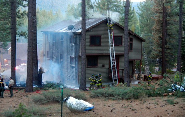Firefighters work to contain a fire that was started Oct. 10 when a plane crashed in El Dorado County. Debris from the plane is in the foreground. Photos/Kathryn Reed