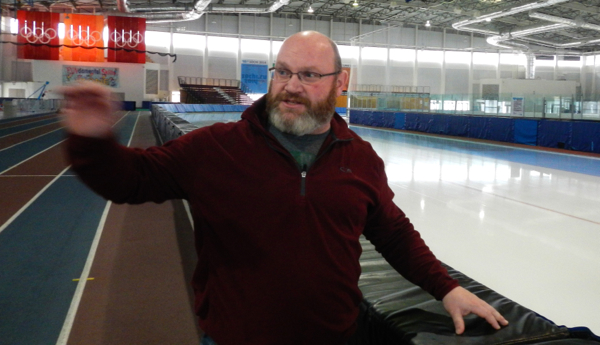 Todd Porter, who oversees the Olympic Oval, stands between the running track and ice for racing. Photo/Kathryn Reed